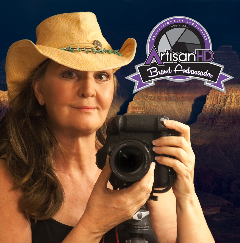 Suzanne Mathia self photo with Brand ambassador badge holding camera and wearing a cowgirl hat