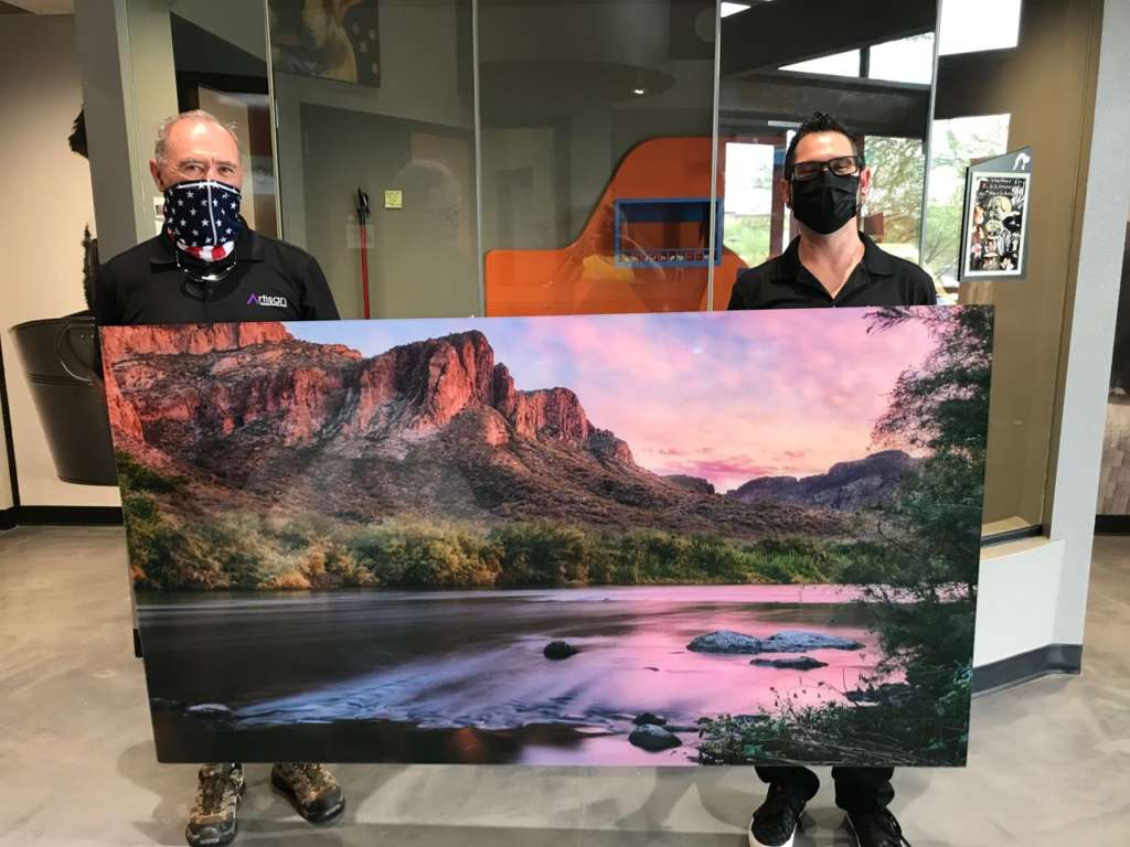 Mike and client holding picture of mountains and lake for acrylic art prints donation to Foothills Animal Rescue